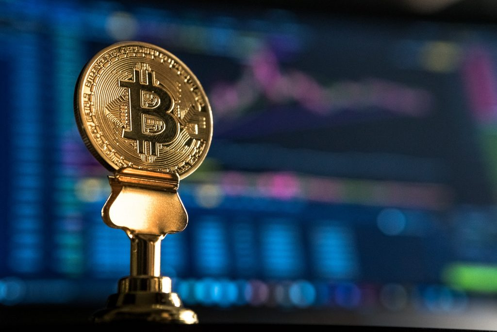 A gold bitcoin with a faded graph in the background