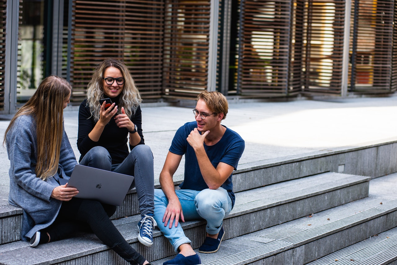 Three young adults sit close to each other on steps outside