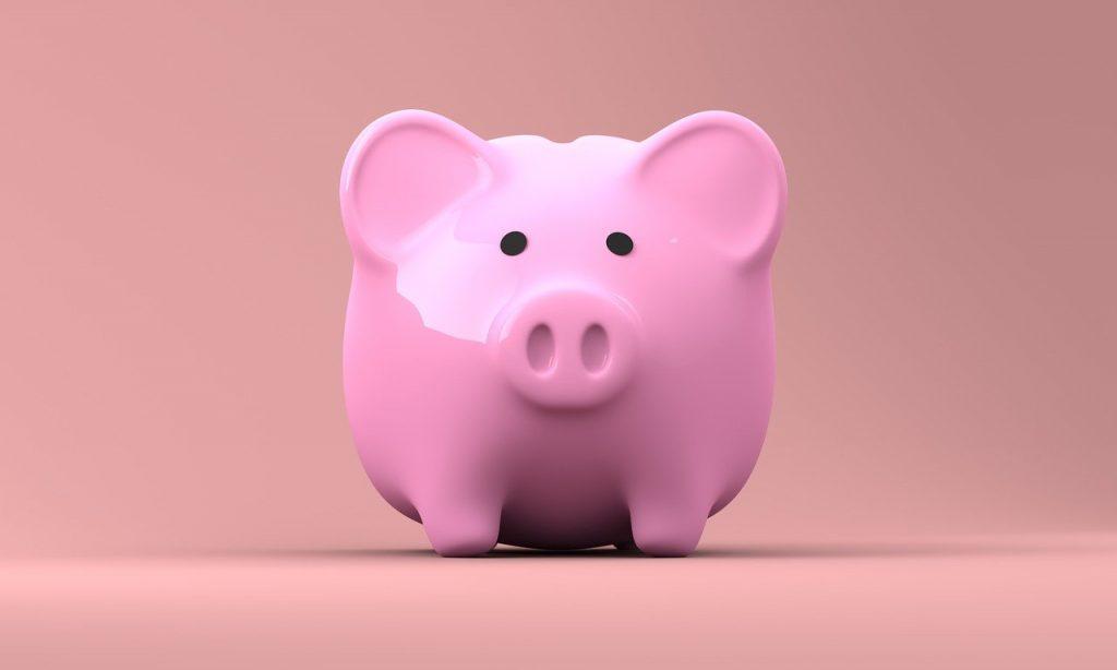 A closeup of a pink piggy bank against a pink background